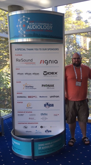Michael standing beside a listing of the sponsors